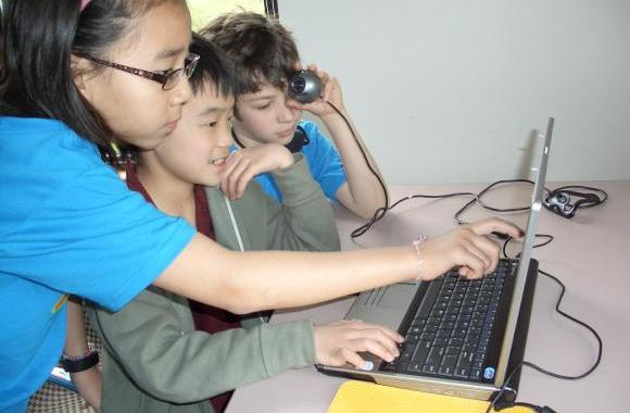 Kids at icamp work on programming a video game.